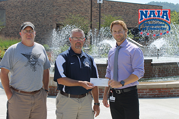 Head men�s soccer coach Ron Goodson and former SSU assistant soccer Bryan Smith present Dr. Nathan Bennington with a check fo