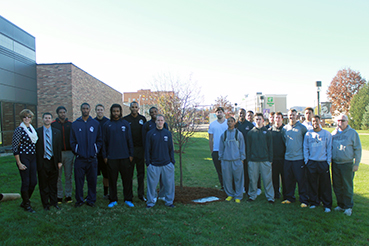 The parents of Sean Elliott and the men's basketball program stand beside the dedication tree.